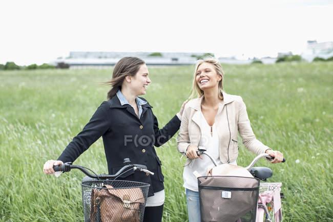 Щаслива молода дівчина з велосипедами на полі. — стокове фото