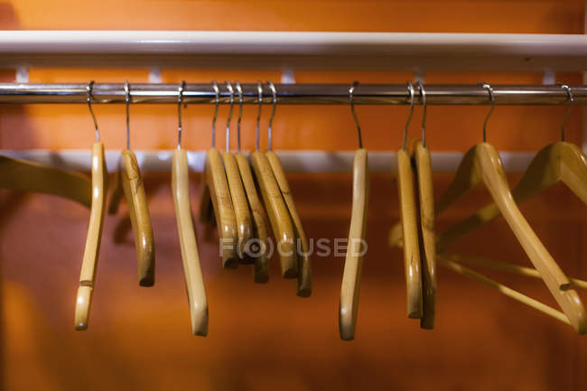 Wooden coat hangers hanging on clothes rack in cabinet — Stock Photo