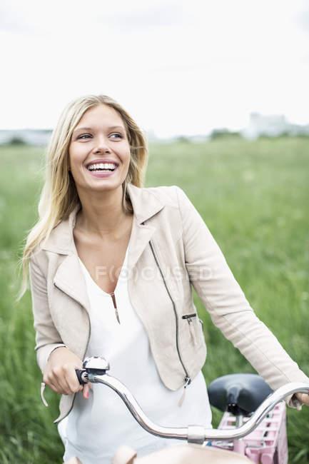 Щаслива молода жінка з велосипедом, стоячи на полі. — стокове фото