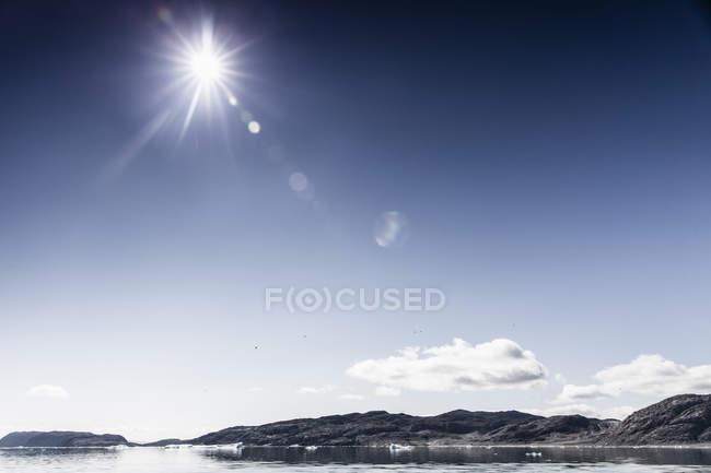 Blick auf Meer und Felsen mit Sonne strahlt hell am sonnigen Tag — Stockfoto