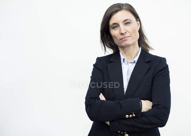 Portrait of confident mature businesswoman standing arms crossed against wall — Stock Photo