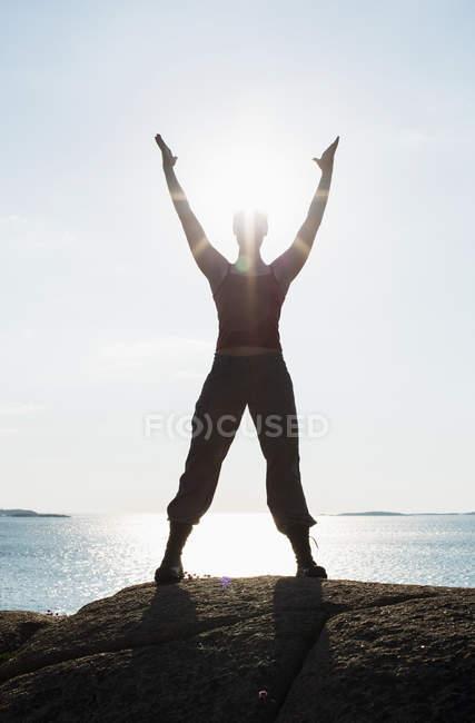 Повна довжина жінка з піднятими руками заняттях йогою на скелі на узбережжі — стокове фото