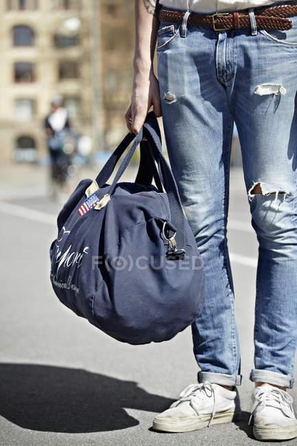 Section basse de l'homme debout avec sac de voyage — Photo de stock
