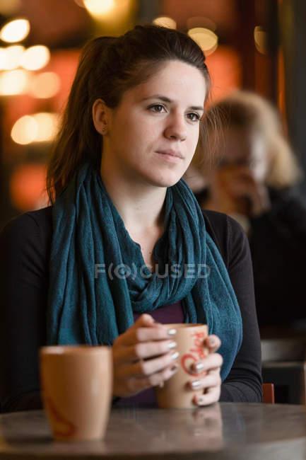 Junge Frau mit Kaffeetasse am Tisch — Stockfoto