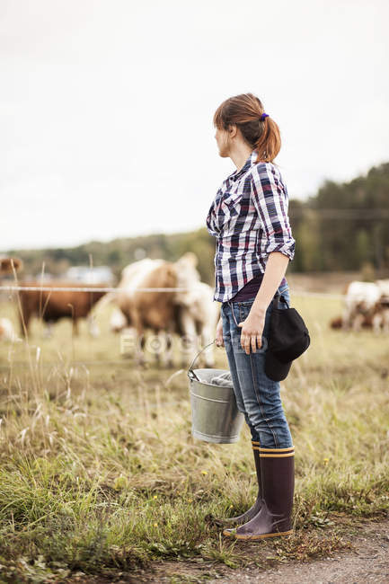 Female farmer with bucket standing on field with animals grazing in background — Stock Photo