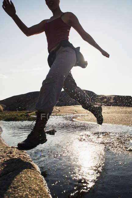Mitte erwachsene Frau läuft im Sommer über Fluss — Stockfoto