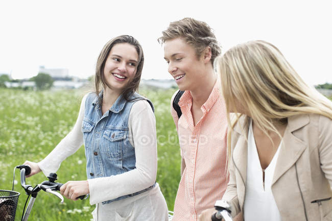 Young friends with bicycles at countryside — Stock Photo