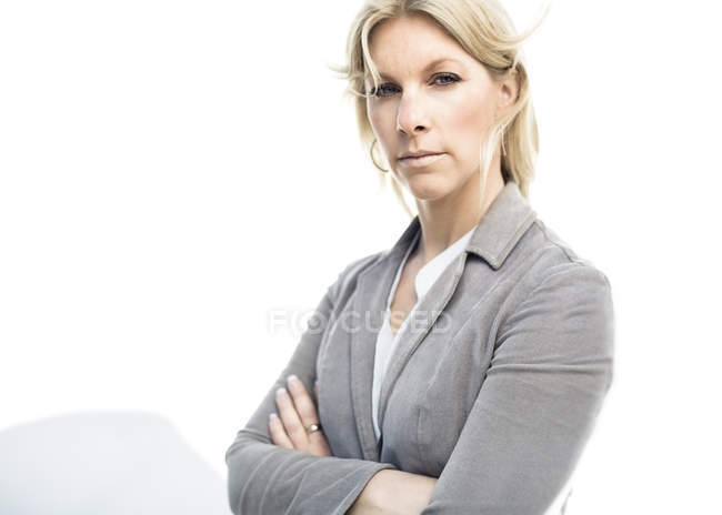 Portrait of businesswoman standing arms crossed against wall — Stock Photo