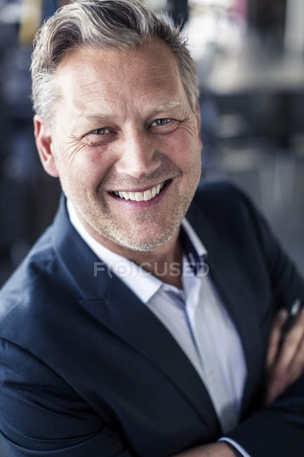 Close-up portrait of mature businessman standing arms crossed in office — Stock Photo