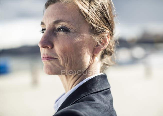 Вид збоку продуманої зрілої жінки дивлячись на відкритому повітрі — стокове фото