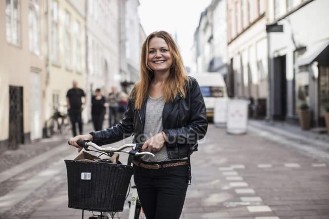 Retrato de jovem feliz com bicicleta de pé na rua da cidade — Fotografia de Stock