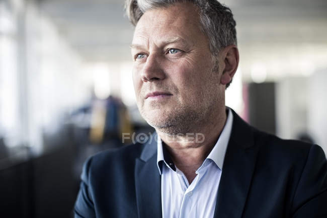 Thoughtful mature businessman looking away in office — Stock Photo