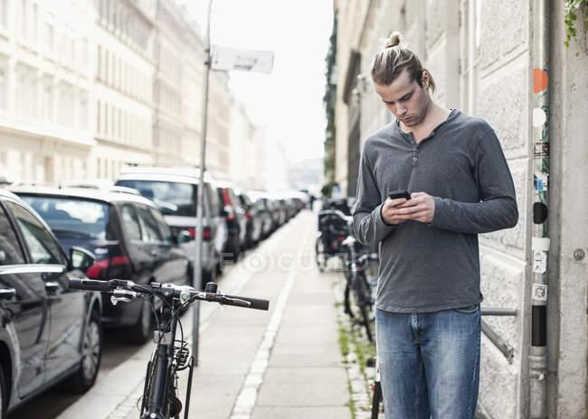 Молодой человек разговаривал по мобильному телефону, стоя на тротуаре — стоковое фото