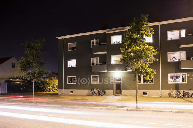 Light trails on street in front of residential building at night — Stock Photo
