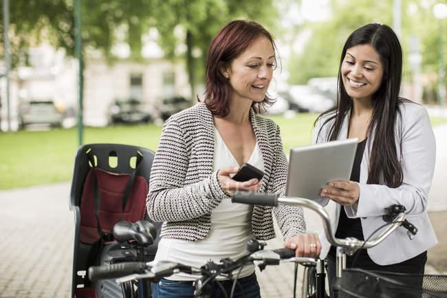 Empresárias felizes com bicicletas usando tablet digital na rua — Fotografia de Stock