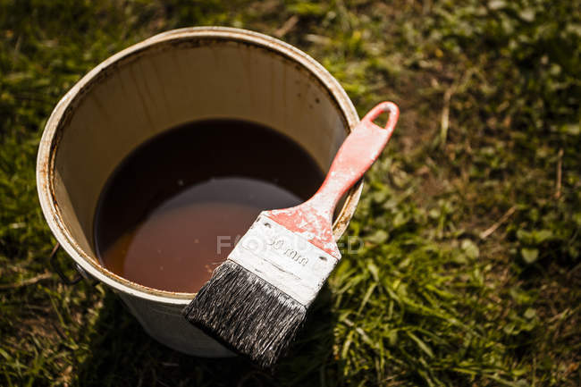 Can of brown paint with brush — Stock Photo