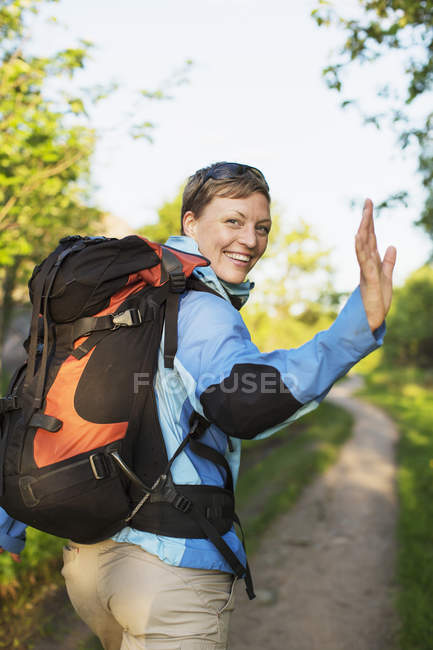 Portrait of happy female backpacker waving while hiking at forest — Stock Photo