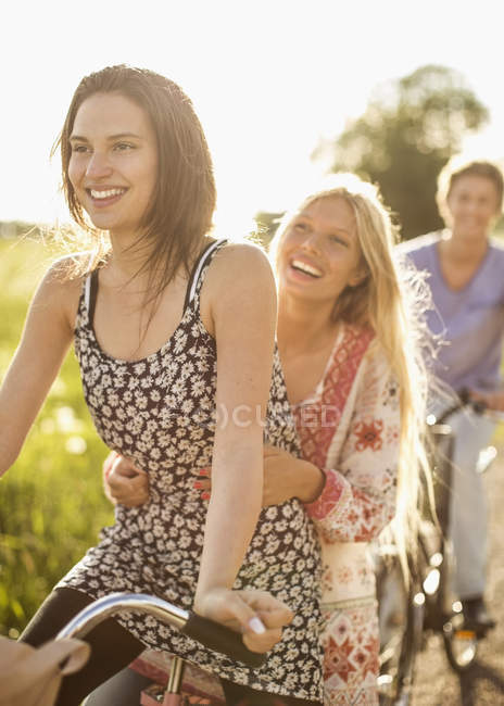Happy friends enjoying bicycle ride at countryside — Stock Photo