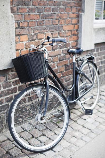 Vélo noir garé près de mur de briques sur la route de la chaussée — Photo de stock