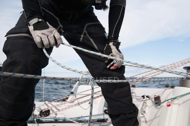 Міделю людини, пов'язуючи мотузку вітрильник — стокове фото