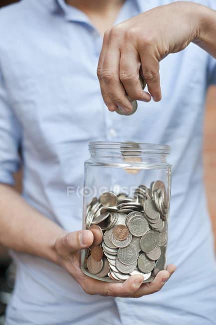Міделю чоловік скидає монети в jar — стокове фото
