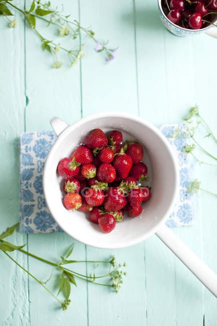 Directamente sobre la vista de fresas en un colador sobre la tabla azul pastel - foto de stock