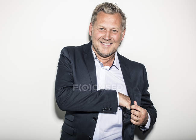 Portrait of happy mature businessman with hand in suit's pocket standing against wall — Stock Photo