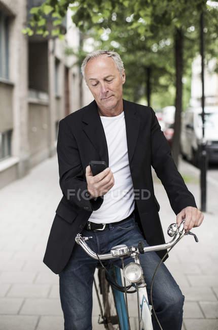 Empresário usando telefone celular enquanto sentado na bicicleta na calçada — Fotografia de Stock