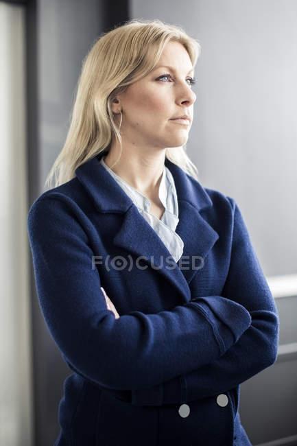 Вдумливий середній дорослий підприємець дивлячись у той час як стоячи в офісі — стокове фото