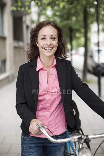 Retrato de mujer de negocios feliz con bicicleta de pie en la acera - foto de stock