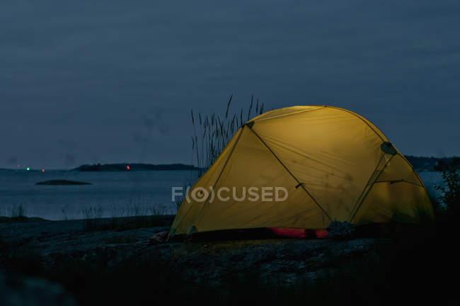 Tente située sur la rive du lac sous le ciel nuageux de la soirée — Photo de stock