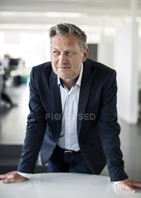 Thoughtful mature businessman looking away while leaning on desk in office — Stock Photo