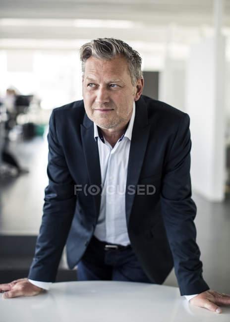 Вдумливий зрілий бізнесмен дивлячись в той час як спираючись на стіл в офісі — стокове фото