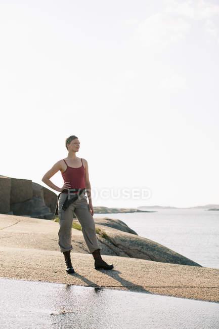 Повна довжина жінка в спортивний одяг стоячи на скелі на узбережжі — стокове фото