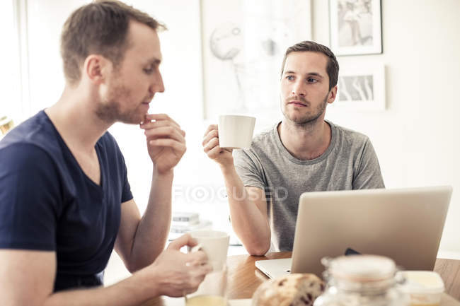 Homosexual couple having breakfast together with laptop at table in home — Stock Photo