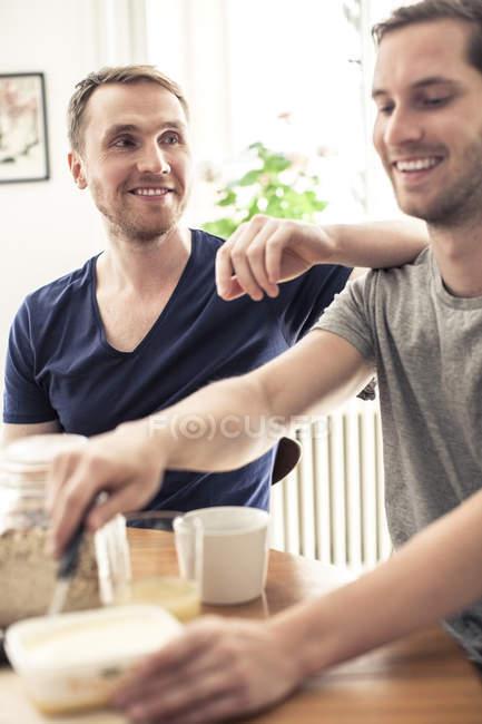 Felice coppia omosessuale fare colazione insieme mentre seduti a tavola — Foto stock