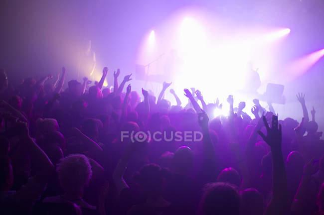 Raggi di riflettori viola sulla pista da ballo affollata al nightclub — Foto stock