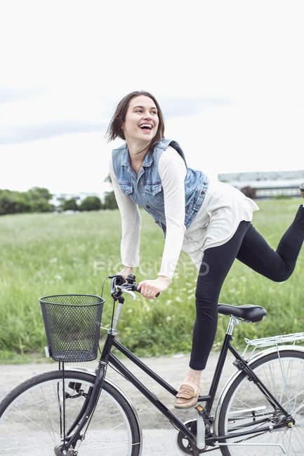 Jovem feliz realizando truque na bicicleta no campo — Fotografia de Stock