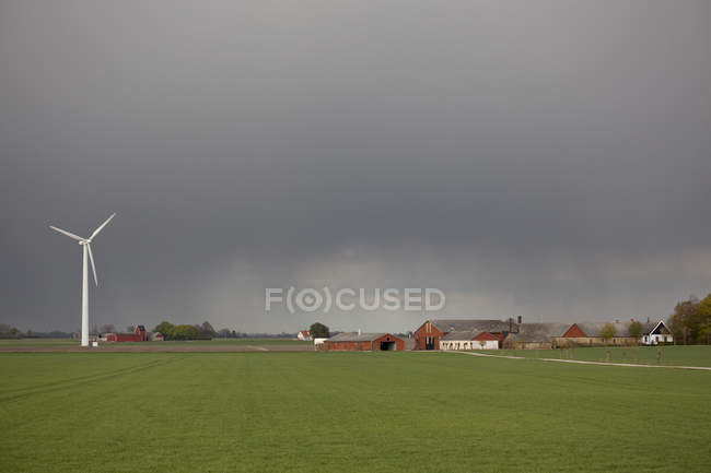 Wind turbine and barns on agricultural field — Stock Photo