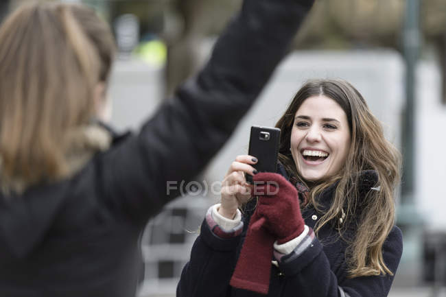 Happy young woman photographing friend through mobile phone — Stock Photo