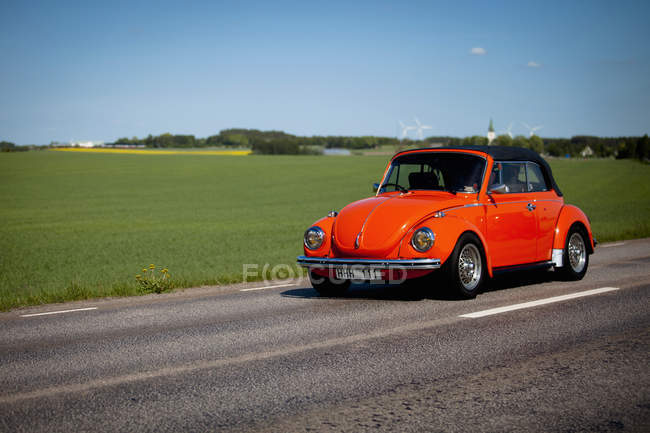 Vista de coche vintage rojo sobre campo verde y camino en el fondo - foto de stock
