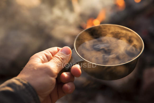 Кампер держит кружку с костром на заднем плане — стоковое фото