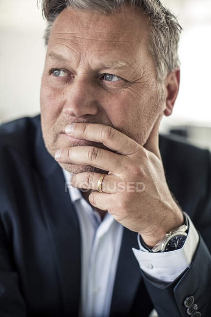 Ragionevole uomo d'affari maturo guardando lontano con mano sul mento — Foto stock