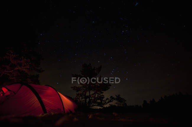 Light in tent against starry night sky — Stock Photo