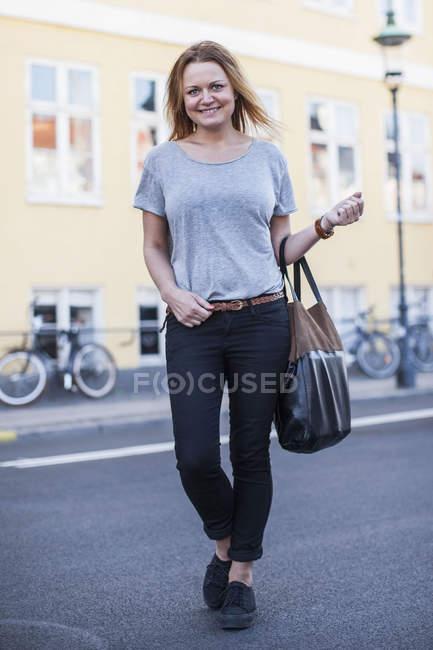 Портрет щасливої жінки, що носить сумочку стоячи на вулицях міста. — стокове фото
