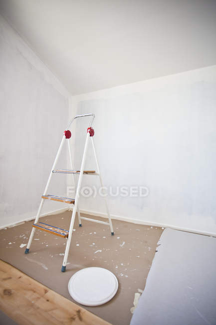 Stepladder in half painted white room — Stock Photo