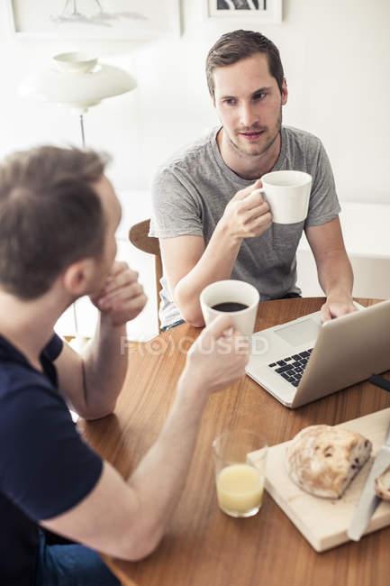 Vista ad alto angolo di coppia omosessuale che fa colazione con computer portatile a tavola — Foto stock
