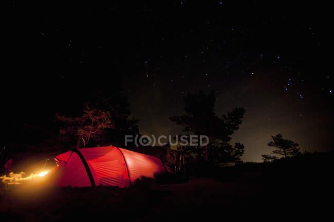 Luz na tenda contra o céu estrelado noite — Fotografia de Stock