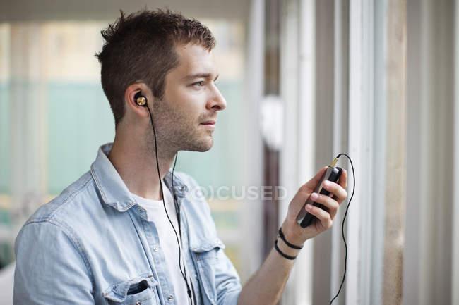 Seitenansicht eines nachdenklichen jungen Mannes, der per Handy Musik hört — Stockfoto