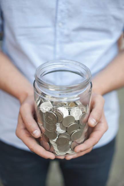 Міделю молодий чоловік тримає jar повний монет — стокове фото